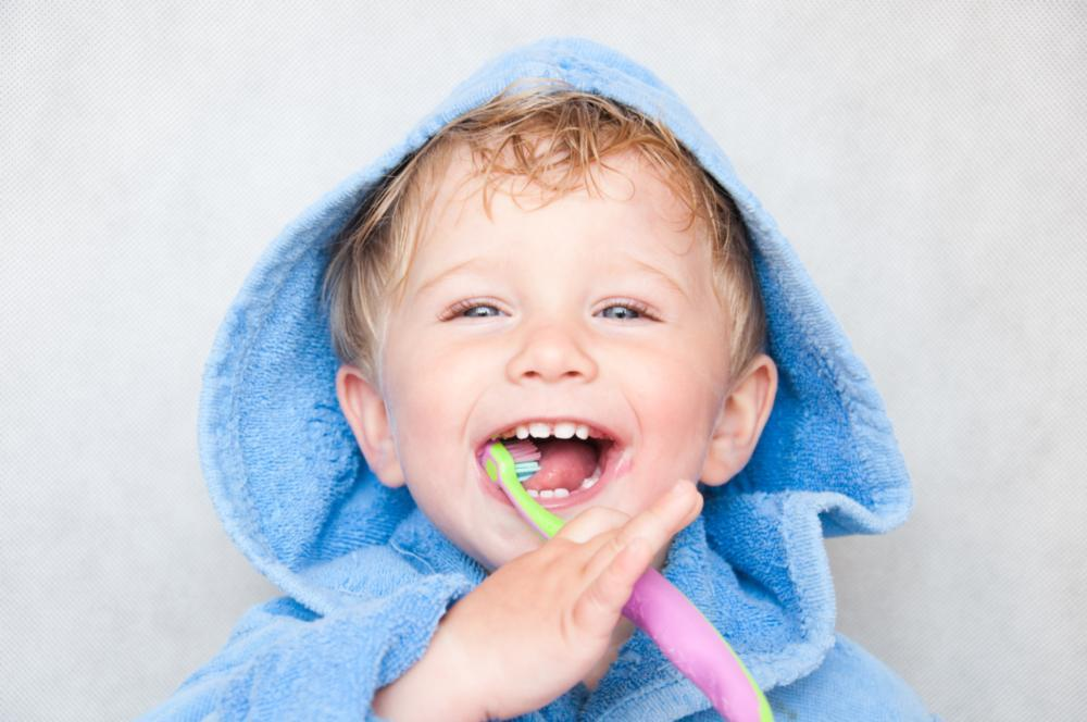 kid smiling with toothbrush | childrens dentistry irvine ca